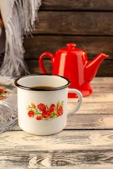 木製の机の上の赤いやかんとコーヒーのカップの正面図