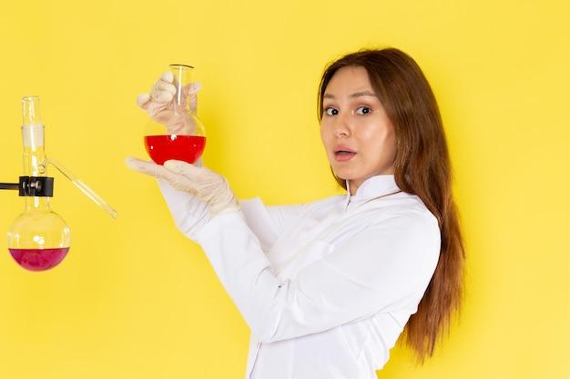 それらを扱う化学溶液を保持している白いスーツの若い女性化学者の正面図