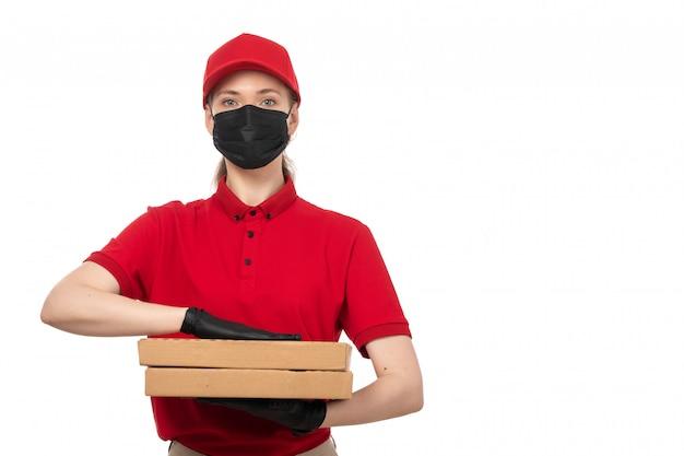 Вид спереди курьер женского пола в красной рубашке, красной шапочке, черных перчатках и черной маске с коробками для пиццы на белом