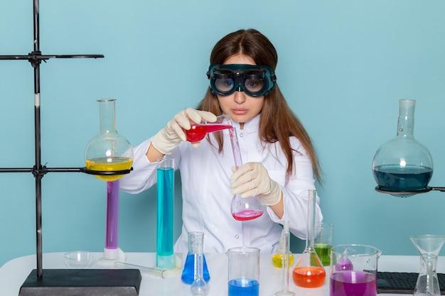 Вид спереди молодой женщины химик в белом костюме перед столом, работающих с решениями