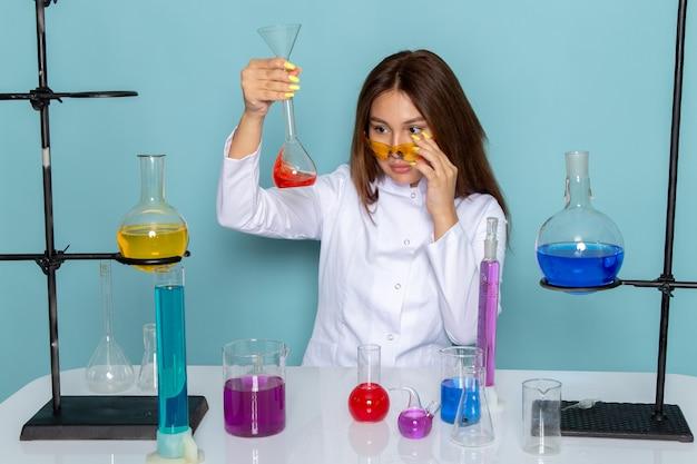 ソリューションを扱うテーブルの前に白いスーツの若い女性化学者の正面図