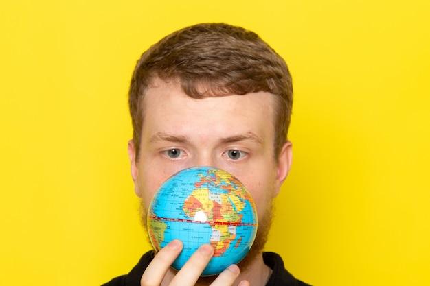 小さな地球を保持している黒いシャツの若い男性の正面図