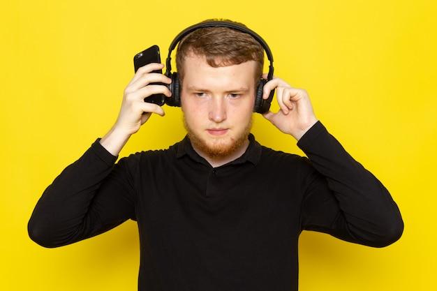 イヤホンを介して音楽を聴く黒いシャツの若い男性の正面図