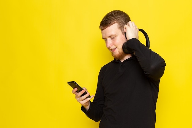 笑顔でイヤホンを介して音楽を聴く黒いシャツの若い男性の正面図