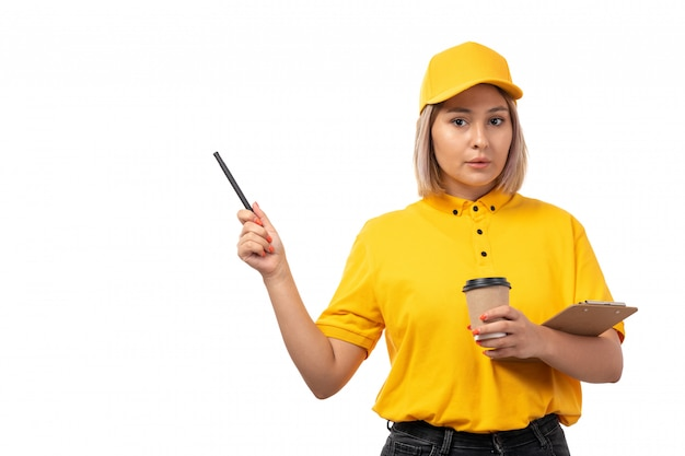 黄色のシャツの黄色のキャップと白のコーヒーペンとメモ帳を保持している黒のジーンズで正面女性宅配便