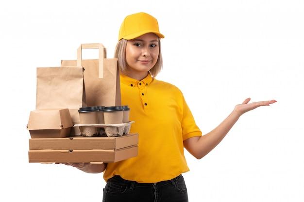 黄色のシャツの黄色のキャップと白に笑みを浮かべてフードボックスを保持している黒のジーンズの正面図女性宅配便