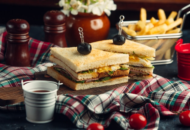 卵、レタス、サラミ、キュウリ、トマトのクラブサンドイッチ、フライドポテト添え