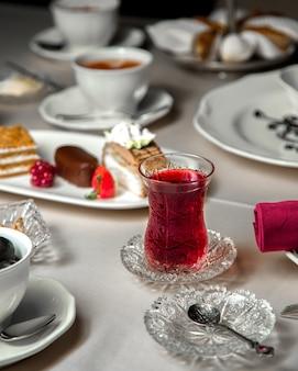 Разнообразный выбор десертов и стакан чая