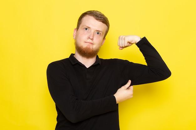 黒いシャツのポーズと屈曲の若い男の正面図