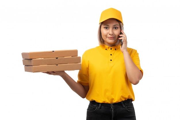 黄色いシャツの黄色い帽子とピザの箱を持って黒のジーンズで正面を向いて女性宅配便ホワイトで笑顔の電話で話しています。