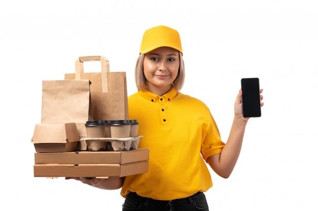 黄色のシャツの黄色のキャップとスマートフォンと白に笑みを浮かべて食物と一緒にボックスを保持している黒いジーンズの正面図女性宅配便