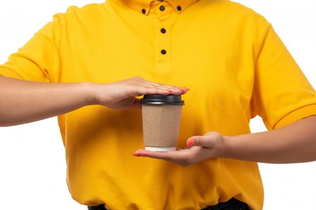 Вид спереди курьер женского пола в желтой рубашке желтой кепке черные джинсы, держа кофе на белом