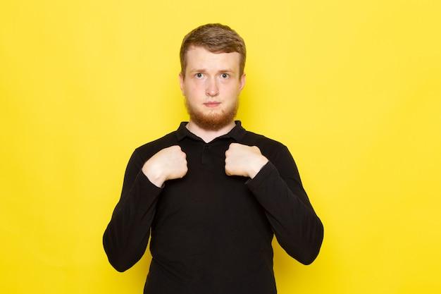 Вид спереди молодого человека в черной рубашке, позируя с выражением