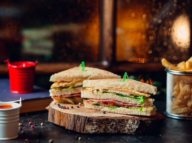 Клубный бутерброд с ветчиной, листьями салата, помидорами, сыром и картофелем фри на деревянной доске