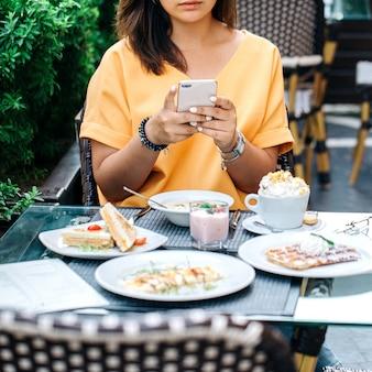 食物と一緒にテーブルの写真を撮る女性