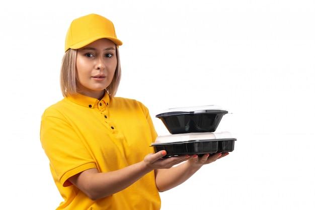Вид спереди курьер женского пола в желтой рубашке желтой кепке, держа миски с едой на белом