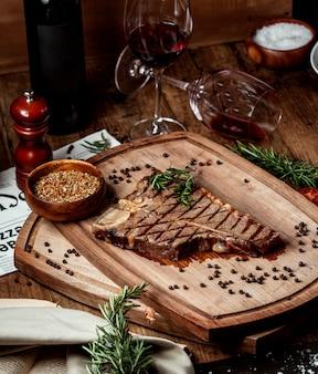 Кусок говяжьего стейка, украшенный сушеными травами и черным перцем