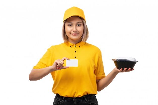 Вид спереди курьер женского пола в желтой рубашке желтой кепке держит белую карточку и миски с едой, улыбаясь на белом