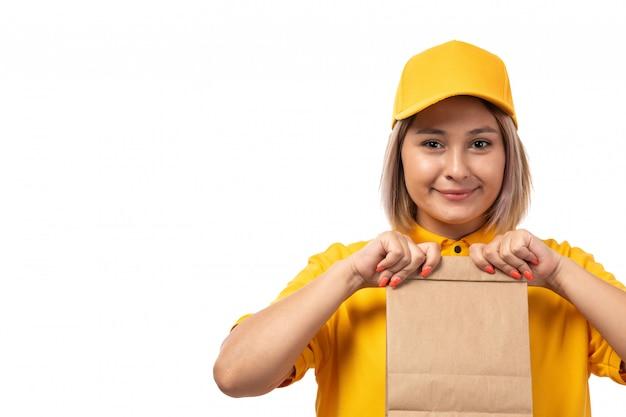 Вид спереди курьер женского пола в желтой рубашке желтой кепке, улыбаясь и держа пакет с едой
