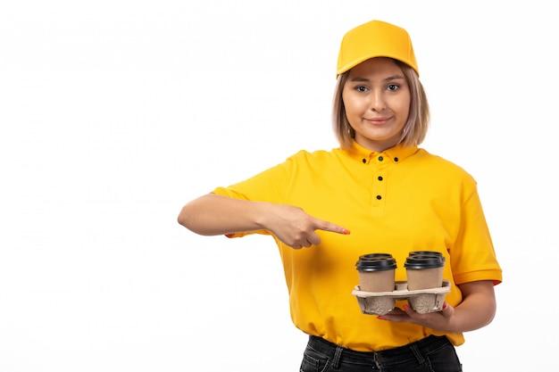 Вид спереди курьер женского пола в желтой рубашке желтой кепке, улыбаясь, держа кофе на белом