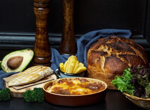 Куриное филе гриль подается с картофелем фри, сковороду с плавленым сыром и булочкой