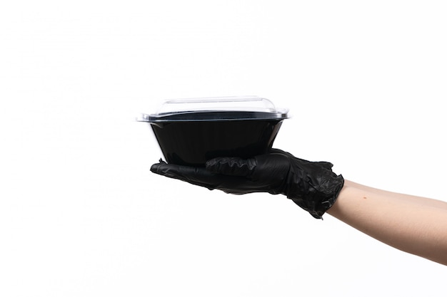 Вид спереди женская рука в черной перчатке держит миску с едой на белом