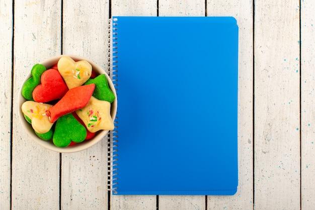 Вид сверху разноцветные вкусные печенья разные сформированные внутри пластины с синей тетрадью на серой поверхности