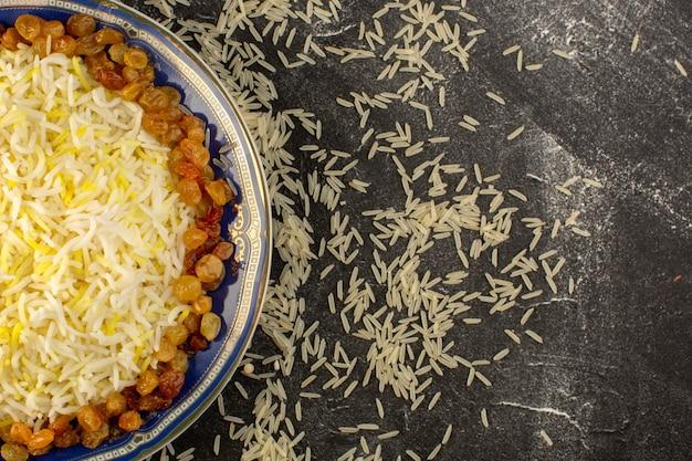 Вид сверху вкусного плова с маслом и изюмом внутри тарелки с сырым рисом на темной поверхности