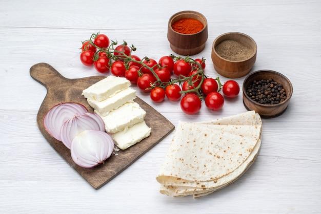 Вид сверху белого сыра с луком и свежими красными помидорами на светлой поверхности