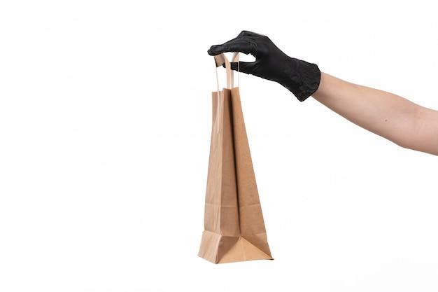 Вид спереди бумажный пакет с пустыми руками, женщина в черной перчатке на белом