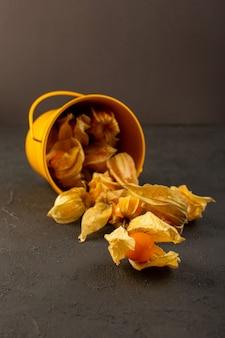 正面図は灰色に分離された黄色のバスケットの中のオレンジ色の果物を皮をむいた