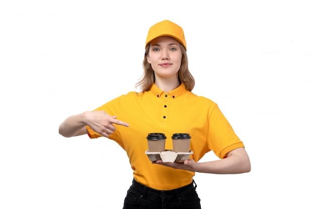 Вид спереди молодой женщины курьер работница службы доставки еды, держа кофейные чашки, улыбаясь на белом