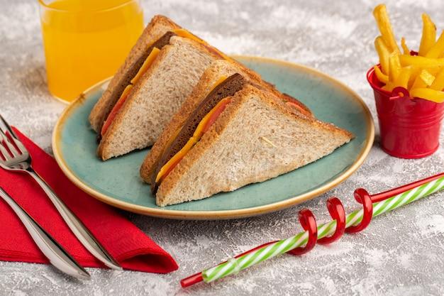 フロントクローズビューおいしいトーストサンドイッチチーズとハムとブループレートの内側にジュースとフレンチフリースナック