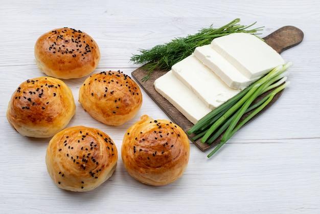Вид спереди булочки с сыром вместе с зеленью на белой поверхности