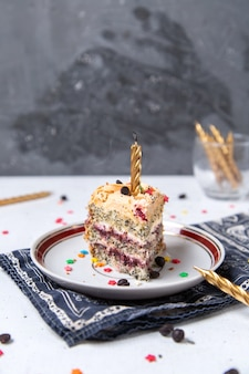 Вид спереди кусочка торта внутри тарелки с горящей свечой