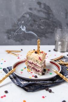 Вид спереди кусочка торта внутри тарелки с потухшей свечой и маленькими звездами украшения на светлой поверхности