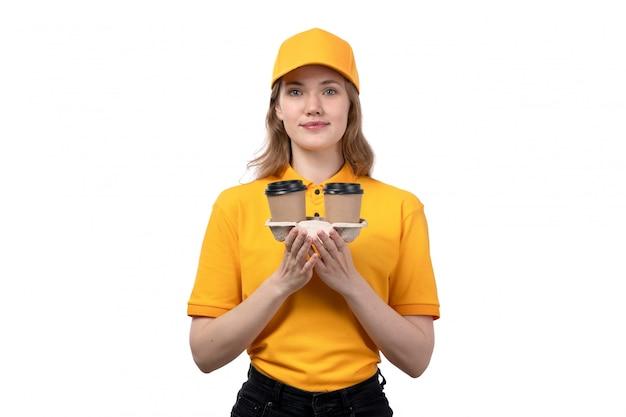 Вид спереди молодая женщина-курьер работница службы доставки еды, держа кофейные чашки с улыбкой на лице на белом