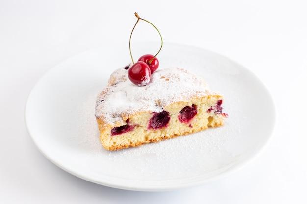 白い表面に砂糖粉末と白いプレート内の桜のケーキのスライスの正面図