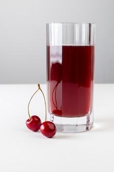 Вид спереди вишневого сока внутри длинного стекла на белом обрамлении