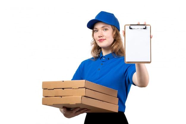 Вид спереди молодой женщины курьер работница службы доставки еды, холдинг коробки доставки еды и блокнот на белом