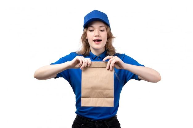 白のフードデリバリーパッケージを保持しているフードデリバリーサービスの正面の若い女性宅配便女性労働者