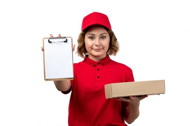 白のフードパッケージとメモ帳を保持しているフードデリバリーサービスの正面の若い女性宅配便女性労働者