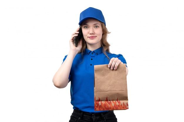 フードパッケージを押しながら白の電話で話しているフードデリバリーサービスの正面の若い女性宅配便女性労働者