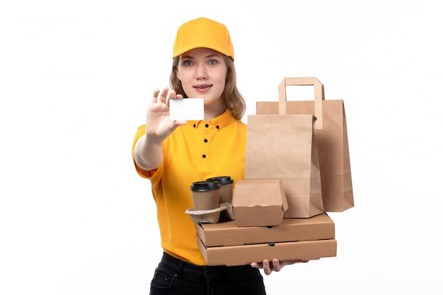 Вид спереди молодая женщина-курьер работница службы доставки еды держит коробки для пиццы кофейные чашки и белую карточку на белом