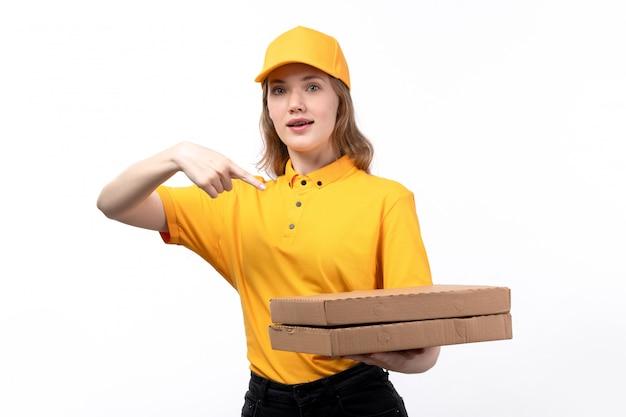 白に笑みを浮かべてピザの箱を保持している食品配達サービスの正面の若い女性宅配便の女性労働者