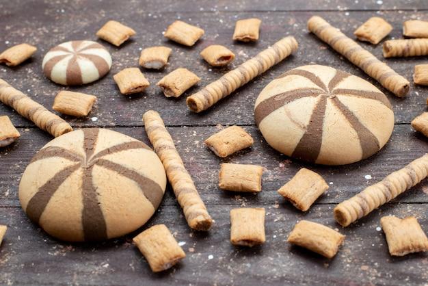 Вид спереди шоколадного печенья круглой и длинной формы на темной поверхности