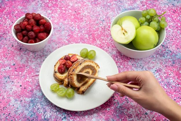 ピンクの机の上のイチゴとリンゴと一緒に白いプレート内のチョコレートロールスライスの正面図