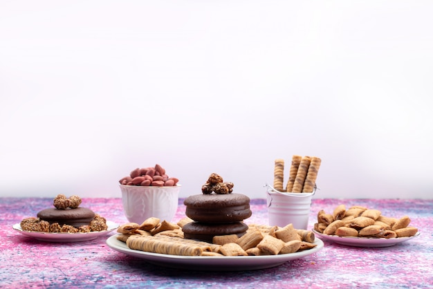 Вид спереди печенья и пирожных внутри тарелок на светлой поверхности