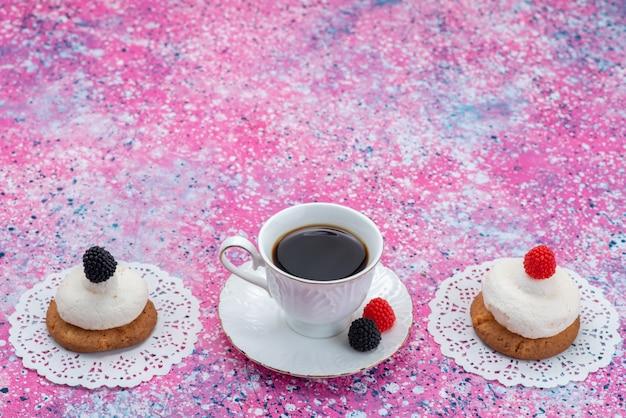 Вид спереди чашки кофе с печеньем и сливками на цветной поверхности