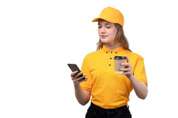 Вид спереди молодой женщины курьер работница службы доставки еды, улыбаясь, держа чашку кофе и с помощью телефона на белом